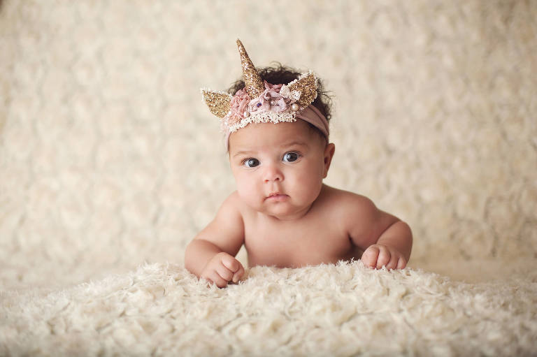 Baby Aari during her three-month milestone session in a glittery unicorn headband.