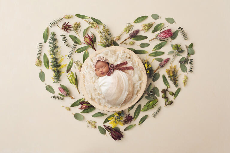 Newborn baby girl Ailani on a backdrop of a floral heart