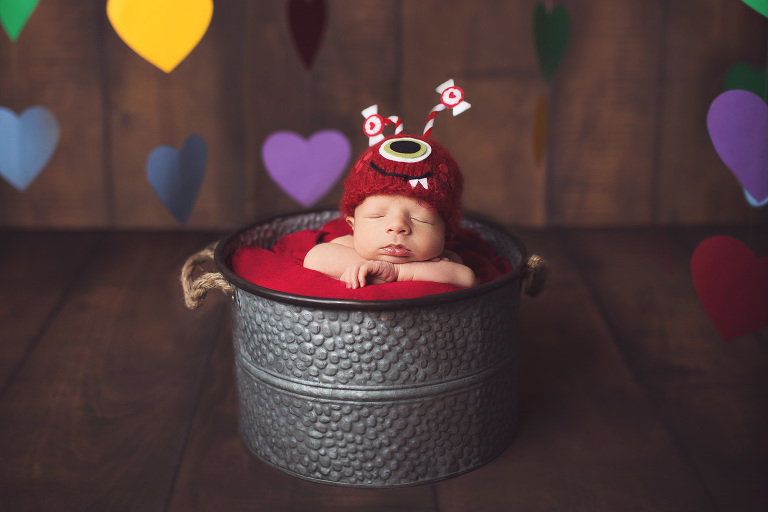 Newborn baby in a bucket with a love monster hat surrounded by floating hearts