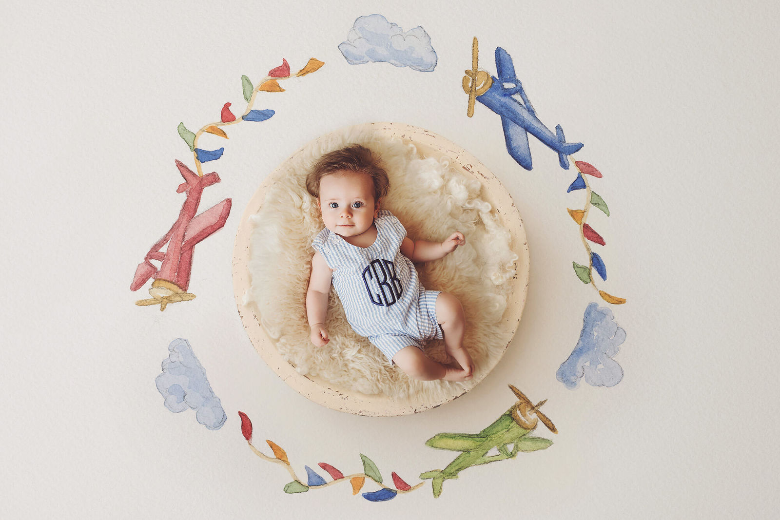 A three-month old baby boy laying in a wooden bowl surrounded by a backdrop of hand-drawn airplanes