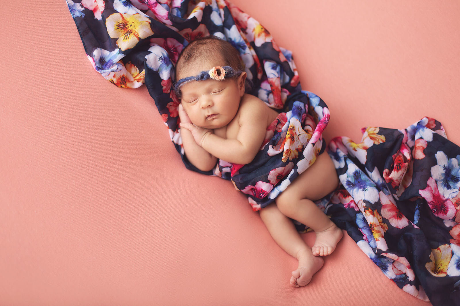Newborn Valentina in a floral wrap and tieback during her Tucson newborn session with Belle Vie Photography