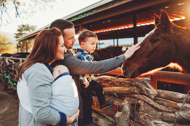 The Schlosser family greets one of the horses at Tanque Verde Guest Ranch during their family photo session