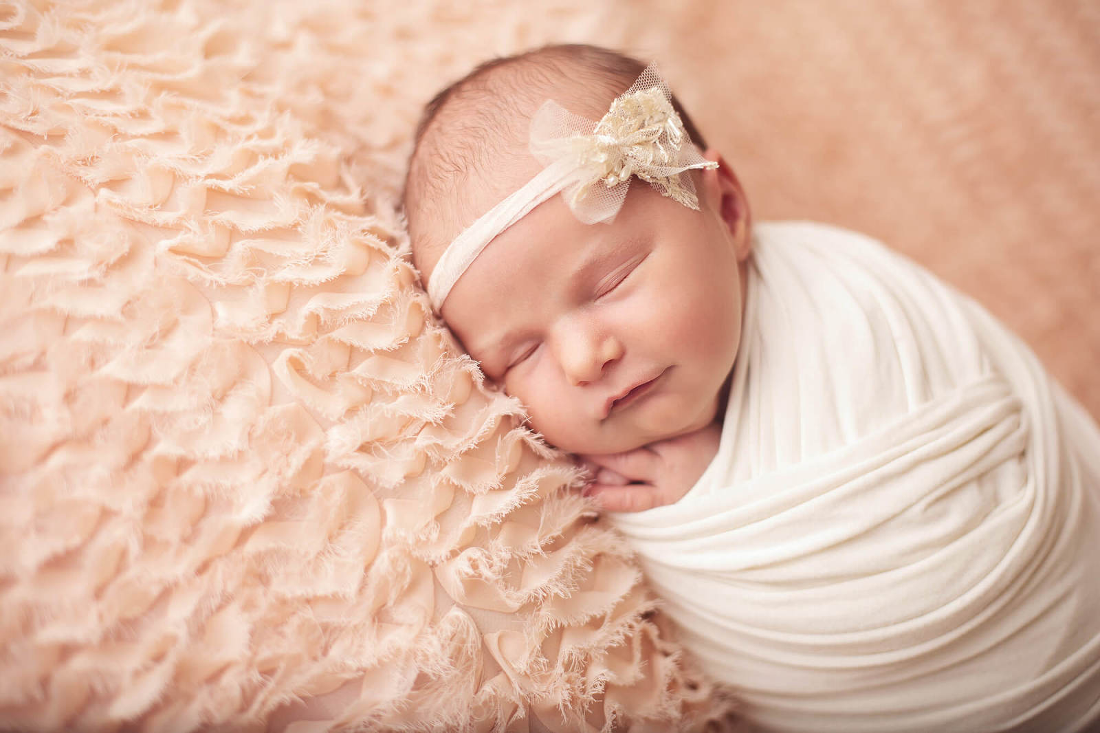 Newborn baby girl smiling with a pearl bow headband during her Tucson newborn session