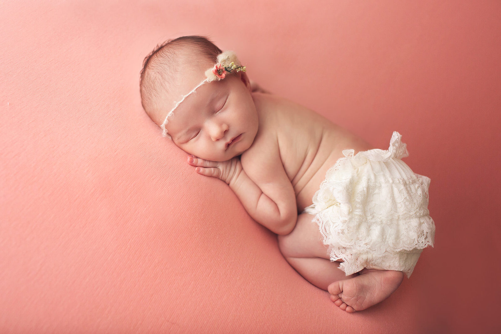 Baby girl on her tummy wearing cream ruffle bloomers and a pink floral headband during her newborn session in Tucson