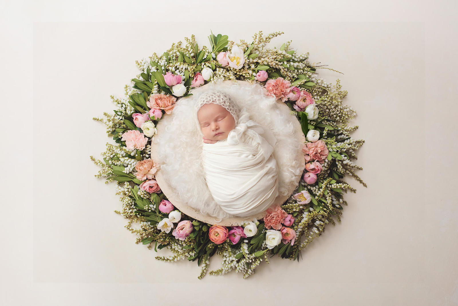 Baby girl during her newborn session laying in a plush nest surrounded by flowers and greenery during her session with Belle Vie Photography in Tucson