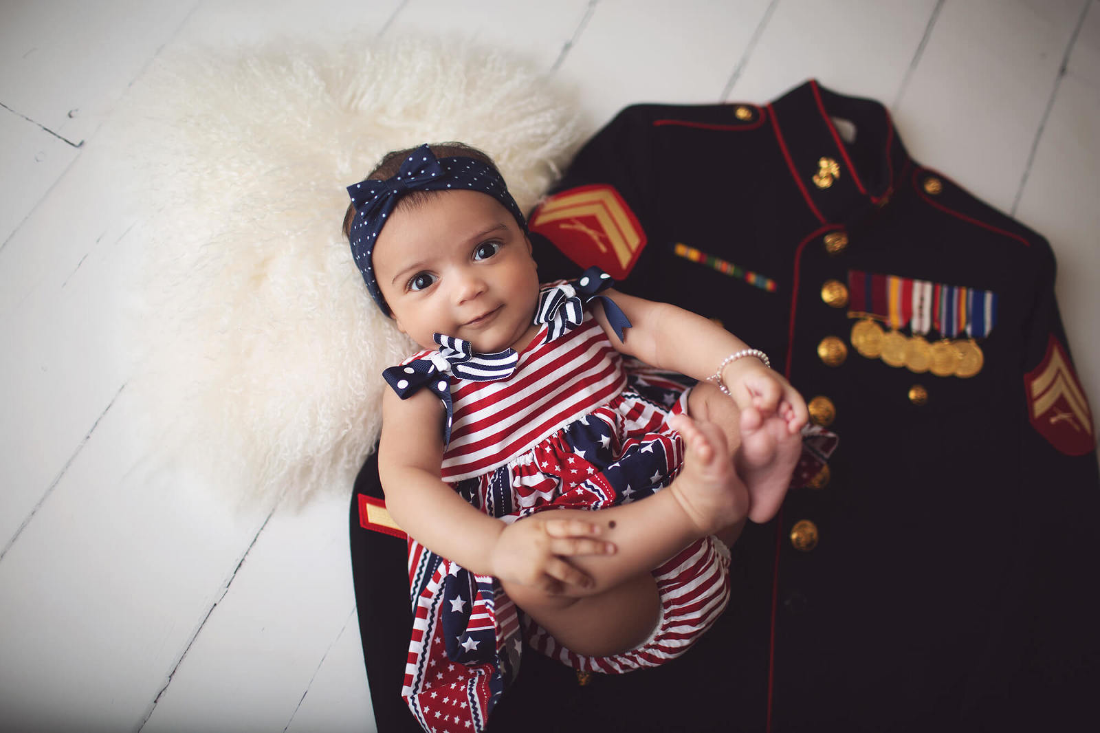 Baby Evelyn during her 3-month milestone session with her daddy's Marine Corps uniform