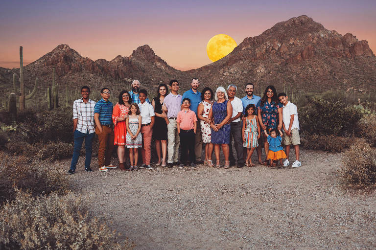 The Castillo family of 18 stands together during their family photo session with Belle Vie Photography as June's Strawberry moon rises above the peaks of Gate's Pass near Tucson