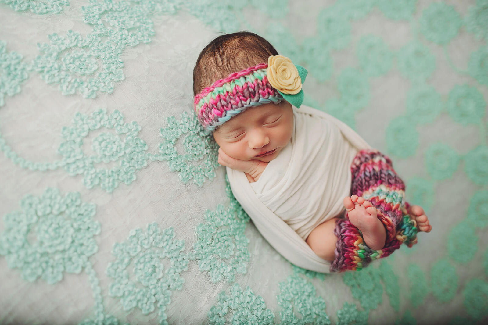 Newborn baby girl wearing leg warmers and a headband during her newborn session with Belle Vie Photography of Wiesbaden