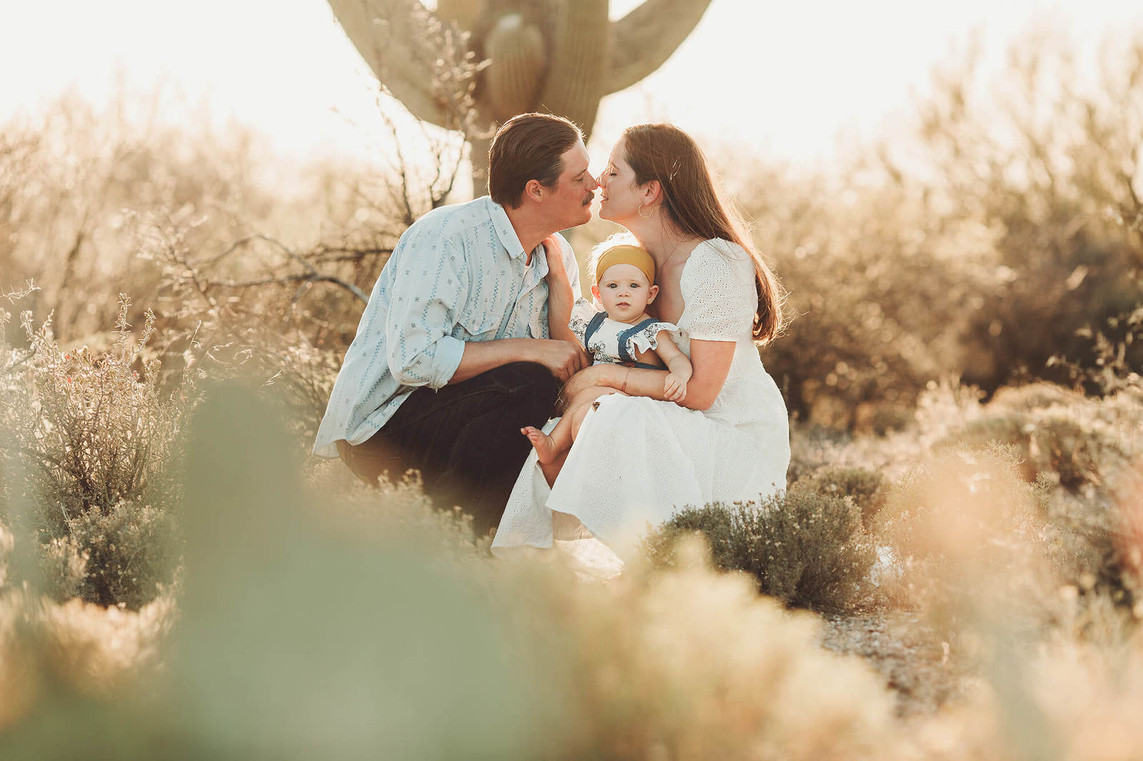 A family of three with mom and dad about to embrace holding their baby daughter under a giant saguaro in Tucson