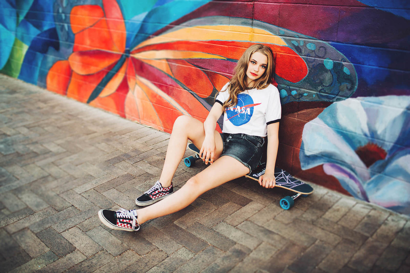 A skateboard senior session for Grace in downtown Tucson in front of a butterfly mural