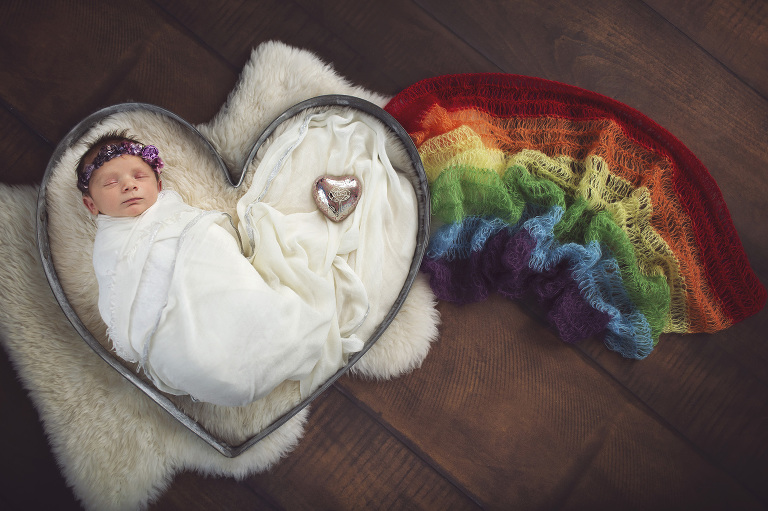 Rainbow baby girl is celebrated during her newborn session