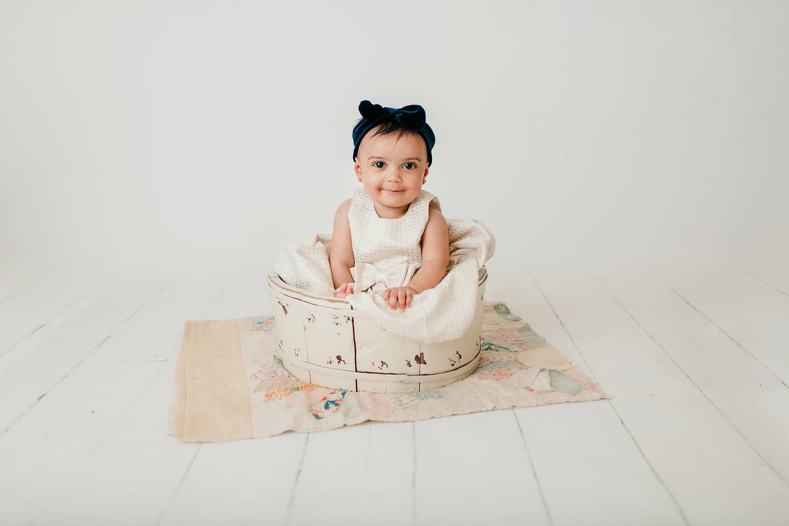 Baby girl sitting in a cream bucket on a quilt during her 6-month milestone studio session