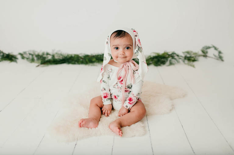 Baby girl in a floral romper with matching bunny ears during her 6-month studio milestone session