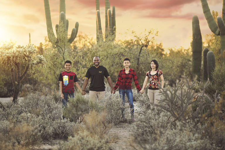 A family of four holds hands amongst the majestic saguaros of Sabino Canyon while looking upon the brilliant Tucson sunset during their family photo session