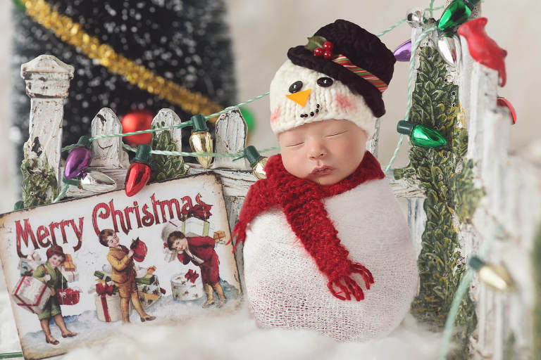 Newborn in a snowman costume sitting next to a Christmas decorated fence by Tucson newborn photographer Belle Vie Photogrpaphy