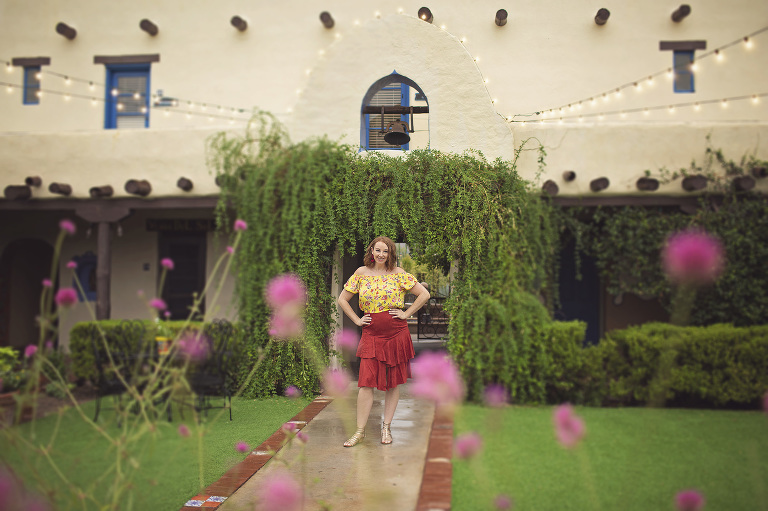 A woman poses in a hotel courtyard surrounded by flowers and greenery during her glamour session at Hacienda Del Sol.
