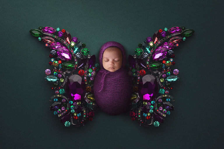 Newborn baby as a gem butterfly
