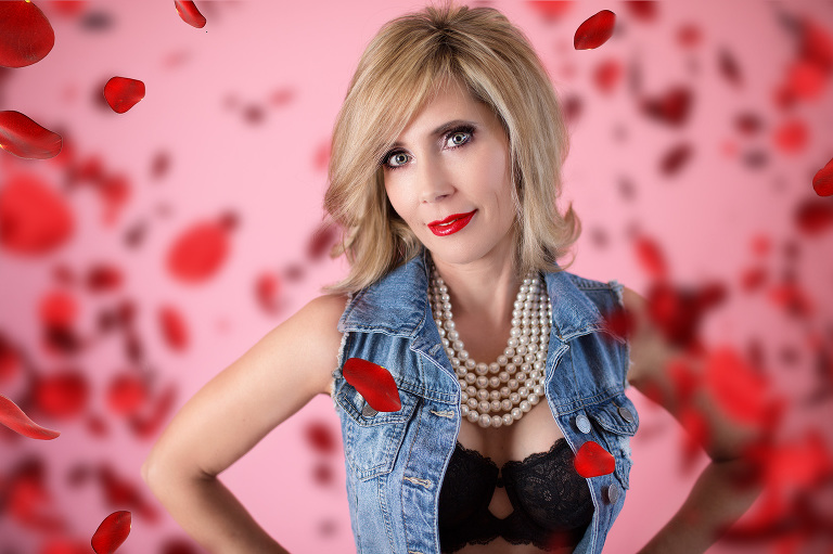 Valentine boudoir photo with woman in pearls and denim as red rose petals fall around her
