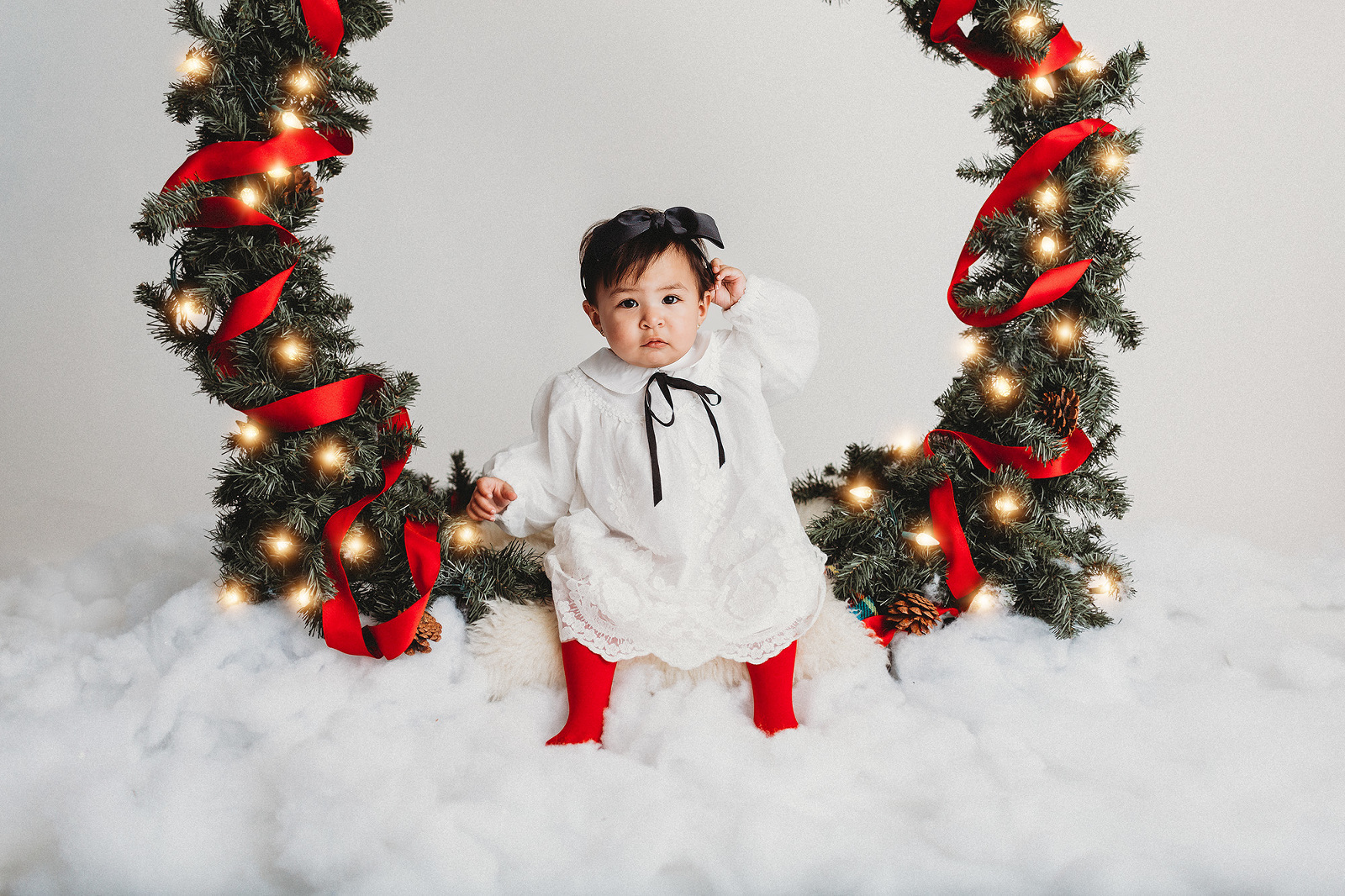 A little girl dressed in her holiday best sits in a giant Christmas wreath during holiday photo sessions with Belle Vie Photography