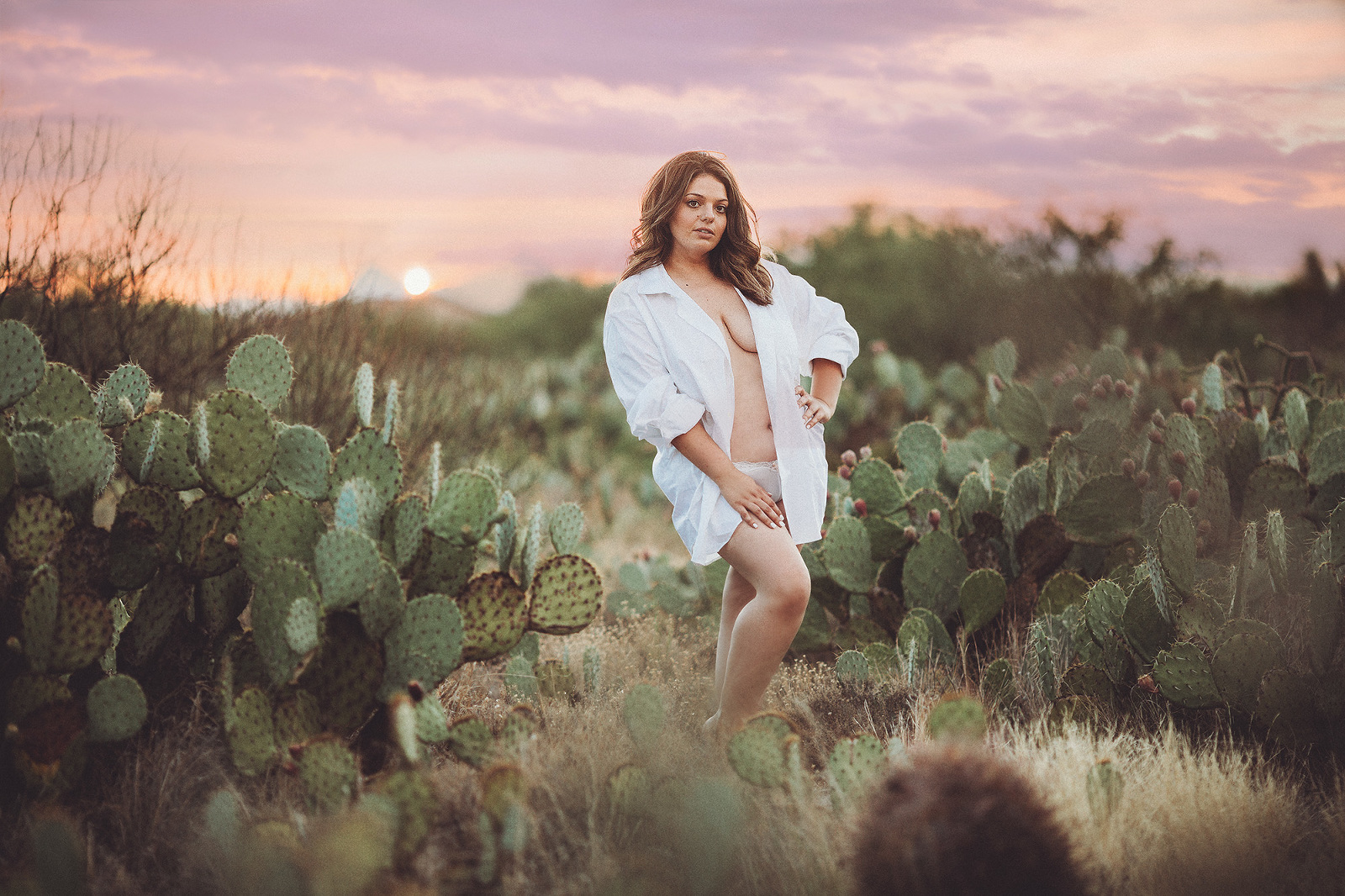 A young woman in a white shirt during her desert sunset boudoir session