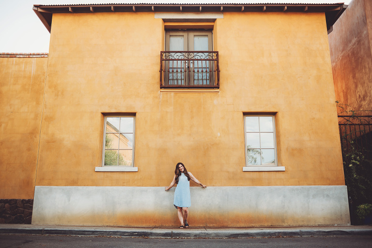 A woman standing next to a traditional-style Tucson home during her portrait session in downtown Tucson