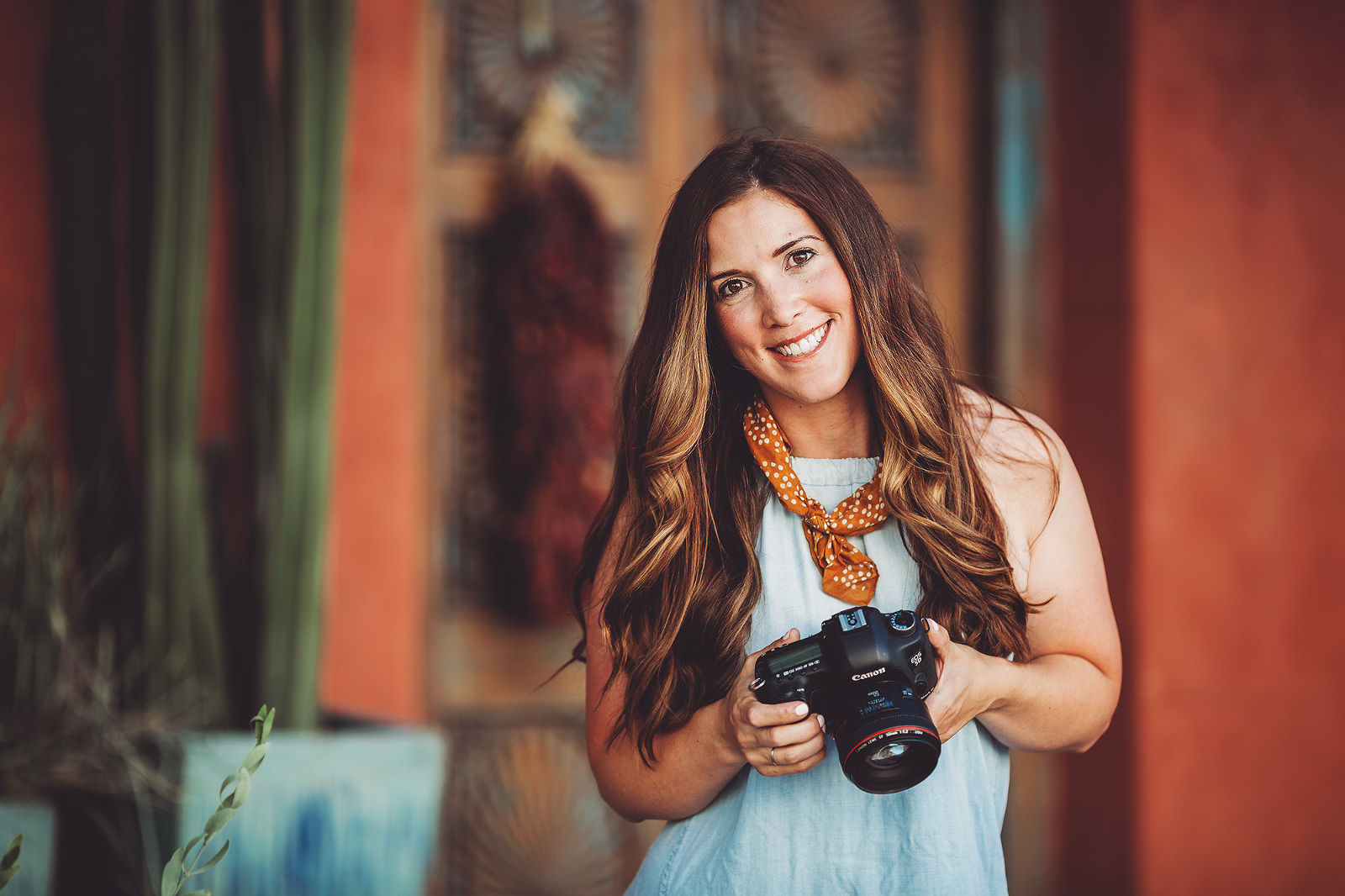 A photographer posing with her camera in a popular Tucson neighborhood during her headshot portrait session