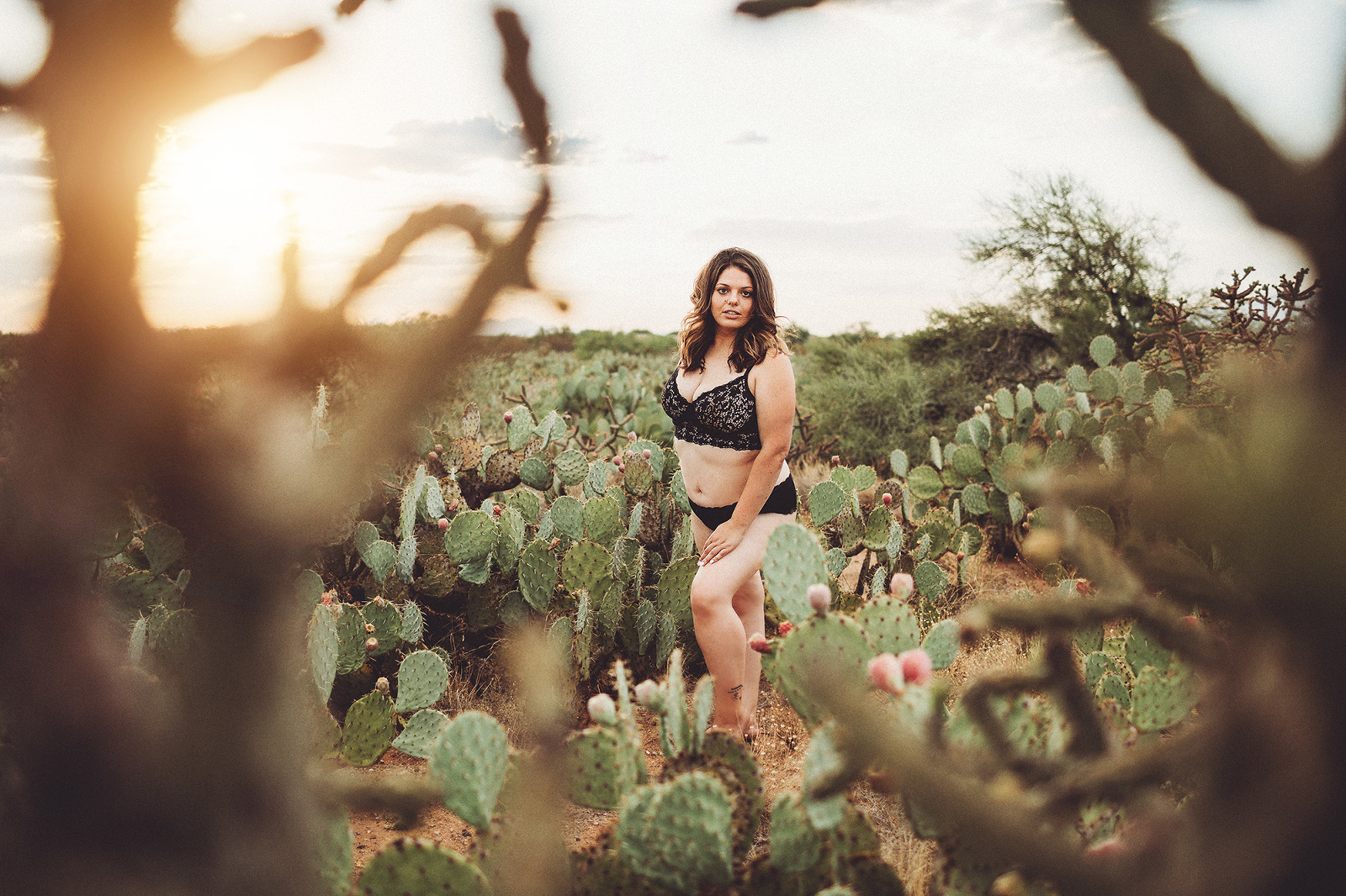 A young woman poses amongst the desert cactus in black lingerie during her desert boudoir session