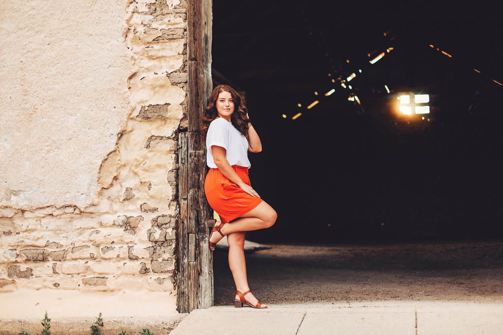 A senior girl leans against a barn entrance playing with her hair as the sun shines through the barn window during her senior session in Sonoita with Belle Vie Photography