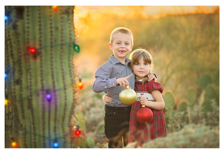 Desert Christmas session with a lighted saguaro and brother and sister holding Christmas ornaments