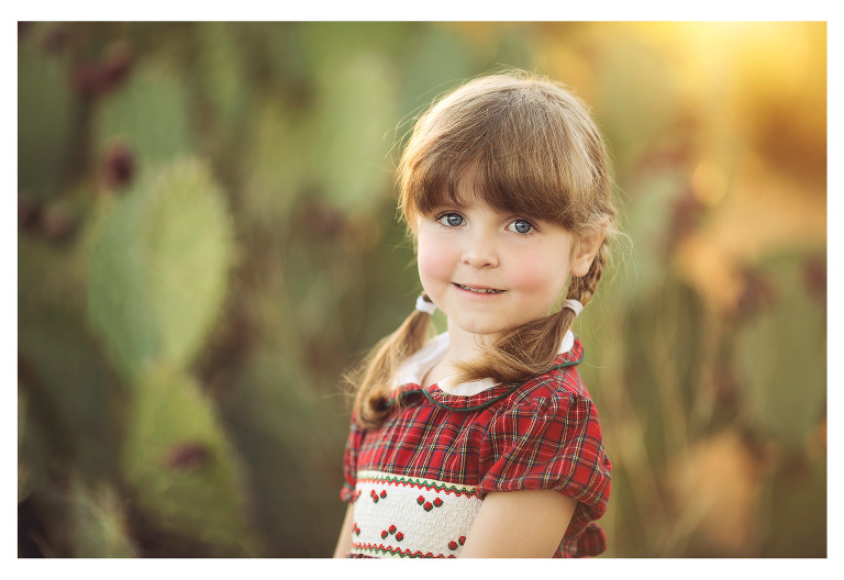 Christmas photoshoot of little girl in a plaid dress and prickly pear cactus during a Tucson sunset