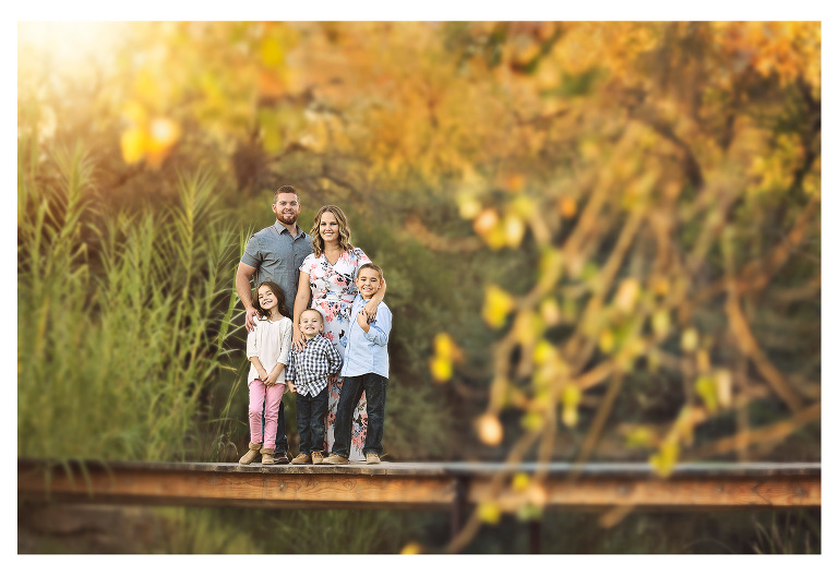 The Elicio family on the bridge at Tanque Verde Guest Ranch framed by fall leaves.