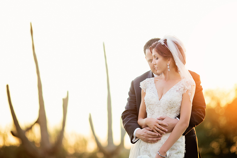 Married couple snuggle at sunset amidst saguaros in Tucson