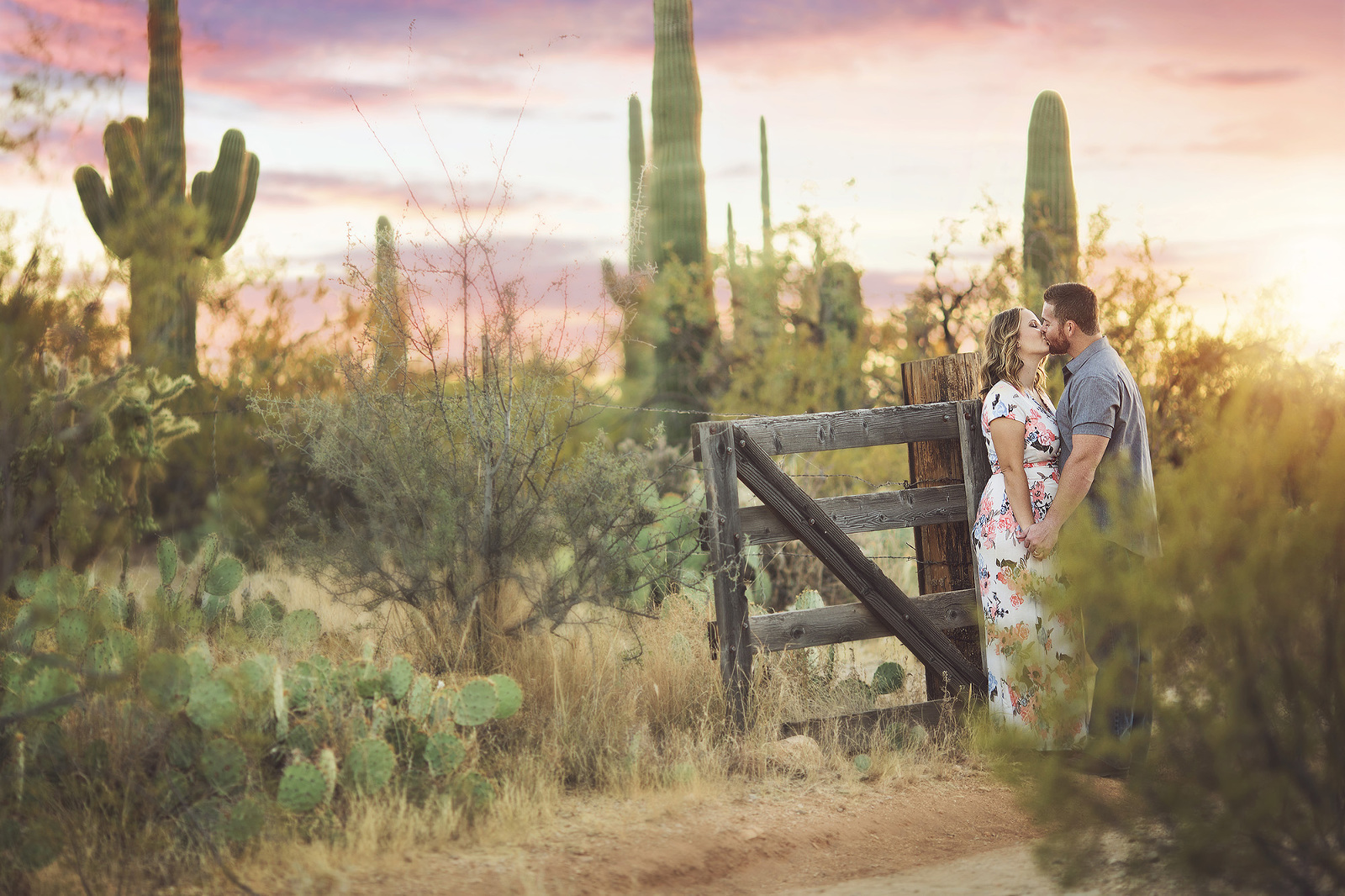 Husband and wife couple kissing during a pink and purple Tucson sunset surrounded by saguaros and cacti