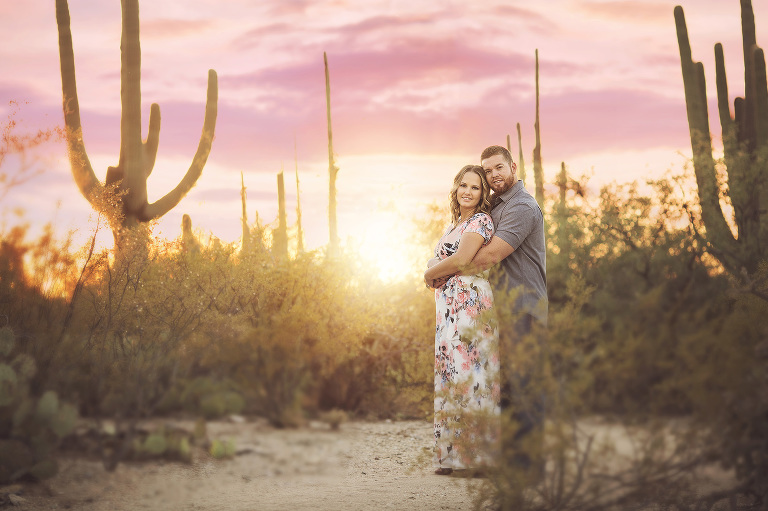 Husband and wife snuggle amidst tall saguaros underneath a pink Tucson sunset