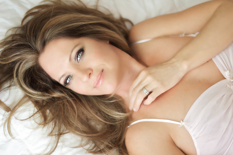 Woman wearing a creamy white camisole laying on a bed during a boudoir photoshoot