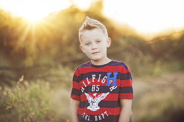 Young boy sporting a Hilfiger tee at sunset in the Sonoran Desert of Tucson for a sunset photo session