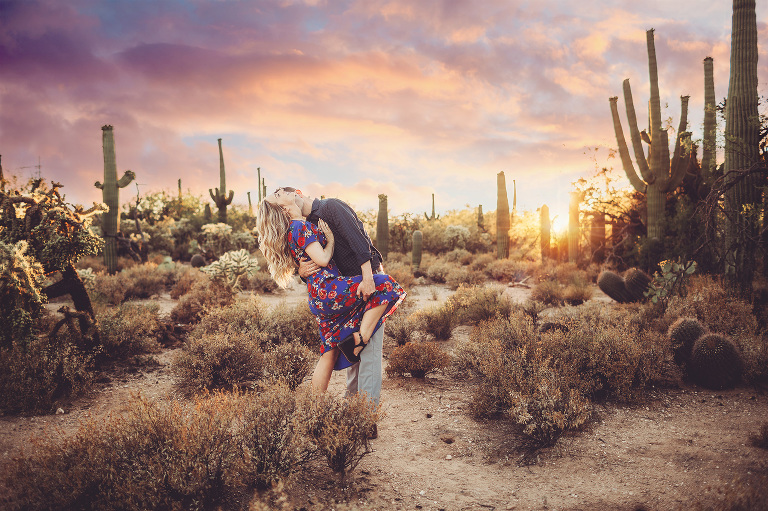 A couple playfully kisses surrounded by saguaros at sunset during their engagement session