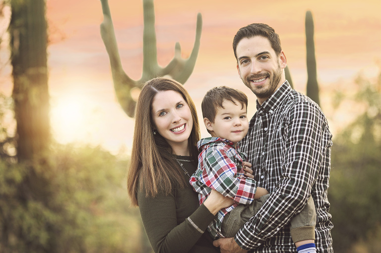 A mom and dad with their son amongst the desert saguaros in Tucson during their holiday family photo session