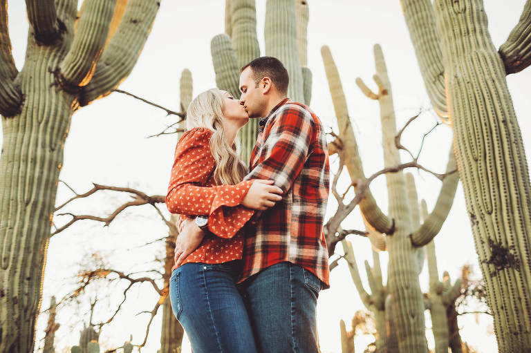 The Freeman's kiss with giant saguaros surrounding them in the warmth of the setting Tucson sun during their couple's session with Belle Vie Photography