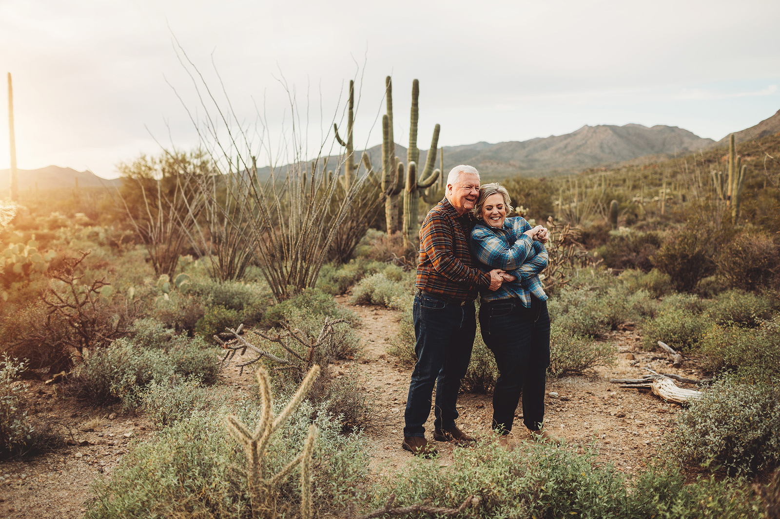 A couple dance together at sunset amongst the saguaros at Gates Pass in Tucson during their 2018 family session