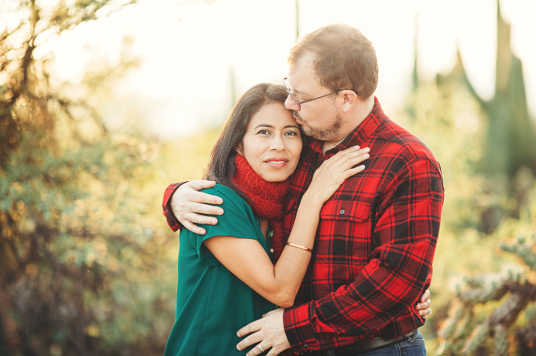 A couple snuggles together for a kiss surrounded by sun and desert foliage during their 2018 holiday photo session with Belle Vie Photography