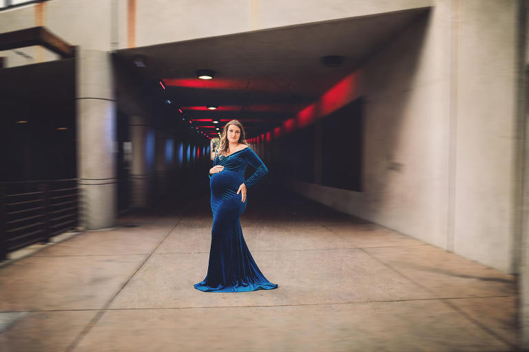 Maternity session in downtown Tucson shot in front of an underpass with red and blue lights