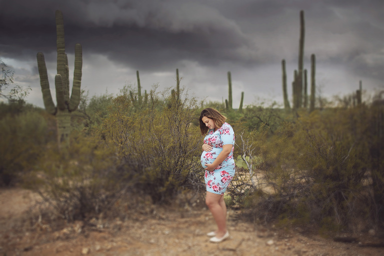 A pregnant mom gazes at her belly with a monsoon storm behind her during her maternity session at Saguaro National Park