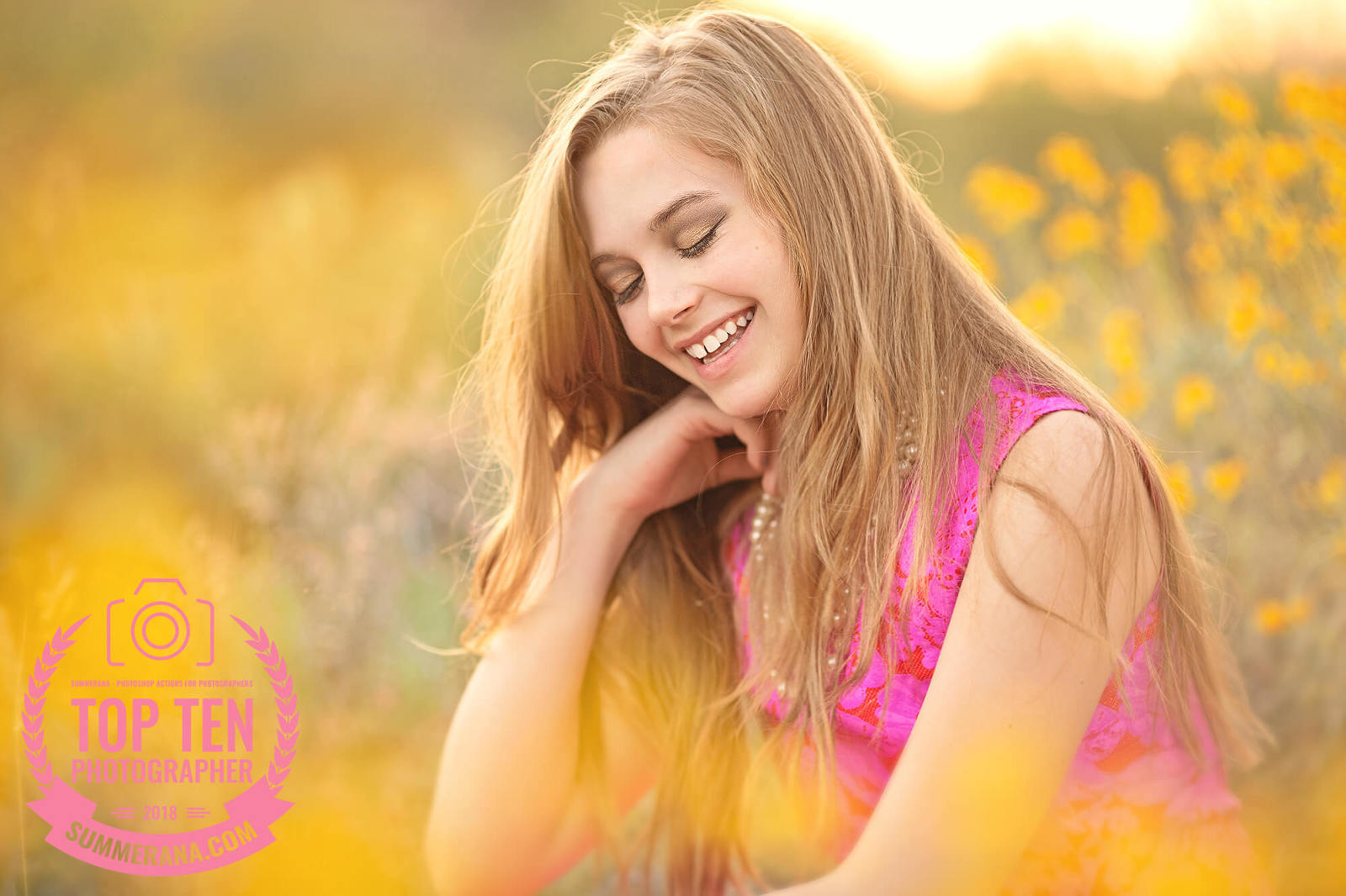 A girl laughs surrounded by yellow spring desert flowers during her senior photo session in Tucson