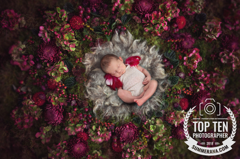 A newborn baby is surrounded by pink and green flowers during her newborn photo session in Tucson