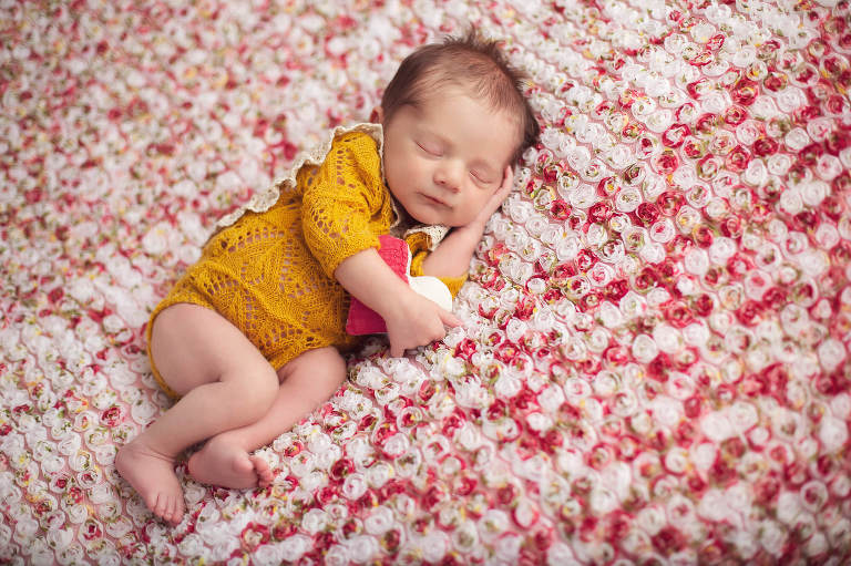 Baby Revy holds a quilted heart during her newborn session in Tucson