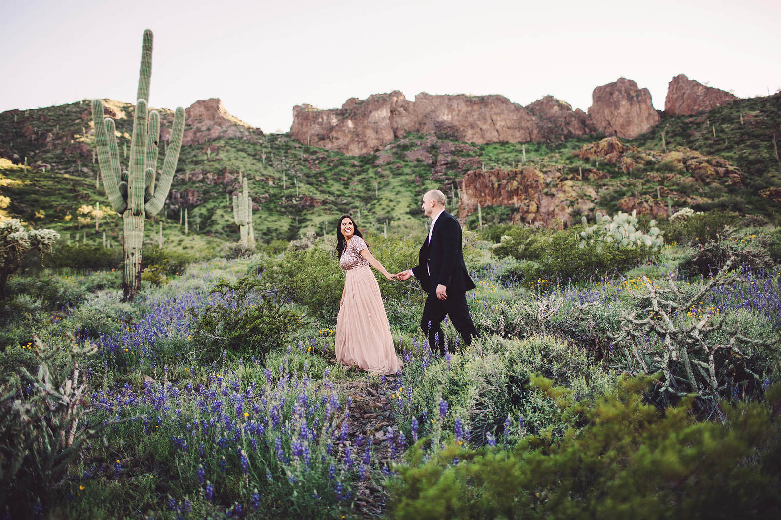 A couple walk amongst the wildflower blooms during their spring engagement session with Belle Vie Photography