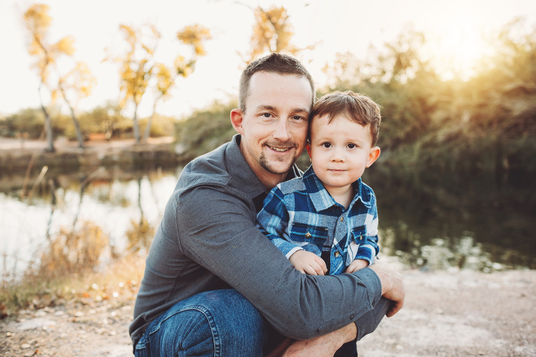 Dad Schlosser holds his oldest son close by the lake at Tanque Verde Guest Ranch during their family photo session