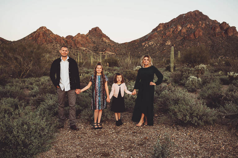 The Gunter family holding hands at sunset with the peaks of Gates Pass at their backs during their snowy desert family session