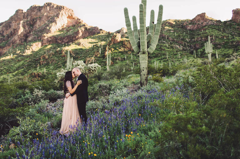 The Paxman's kiss surrounded by wildflowers and Picacho Peak in the background during their wildflower couple's session